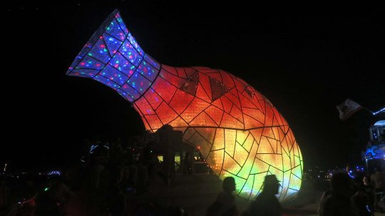 Vase mutant vehicle lit up at night at Burning Man.