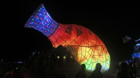 Vase mutant vehicle lit up at night at Burning Man.