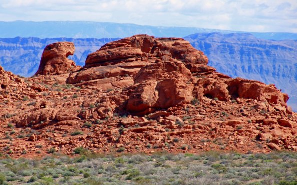 Distant mountains add contrast and depth to the bright red sandstone. (Photo by Peggy Mekemson.)