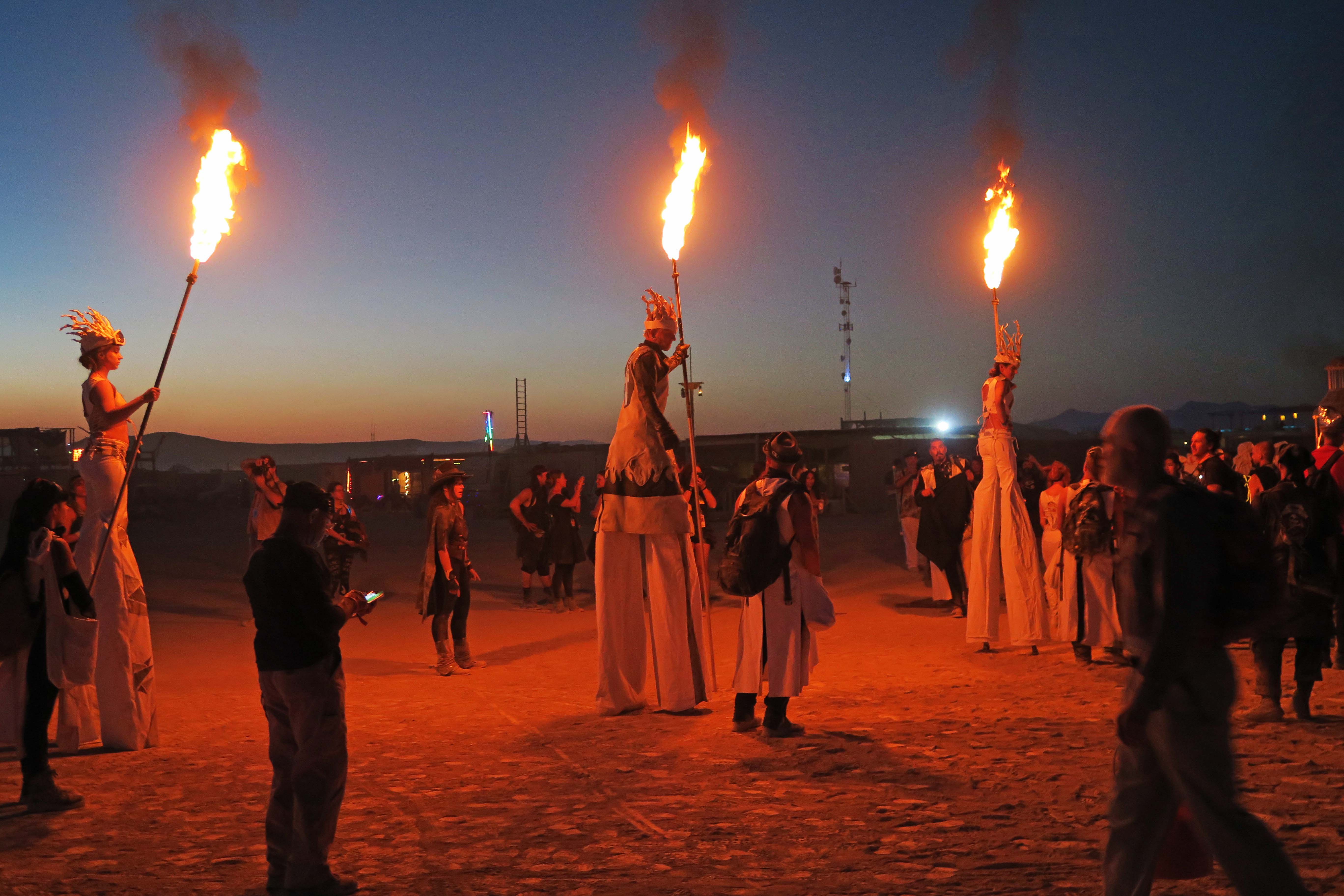 Stilt walkers on way to lighting of the Man, Burning Man 2017