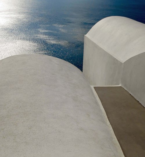 Photo of rounded buildings on Santorini overlooking Aegean Sea by Curtis Mekemson.