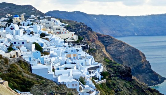Photo of buildings on cliff in Santorini by Curtis Mekemson.