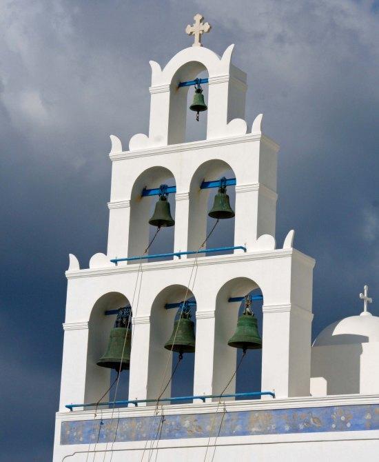 Church bells against dark sky in Santorini