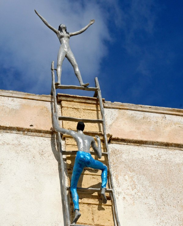 Climbing a ladder in Santorini