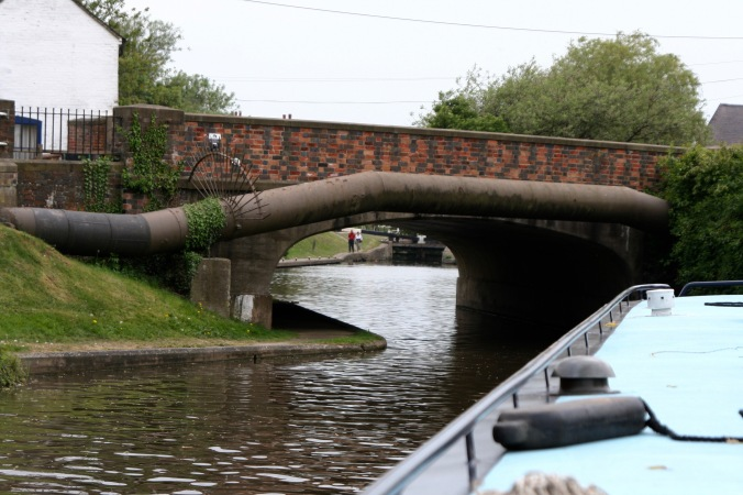 Piloting narrowboat under bridge on Trent and Mercy Canal