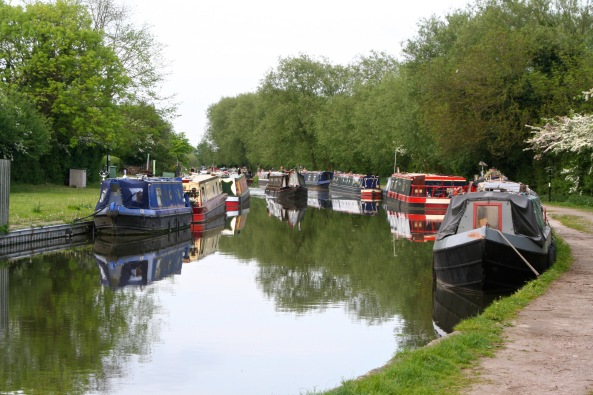 Piloting past moored boats while metting another boat on Trent and Mercy Canal