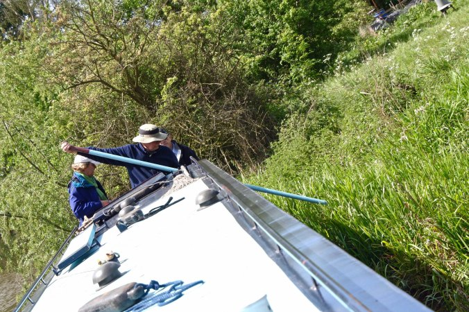 Poling narrowboat off shore on Trent and Mersey Canal