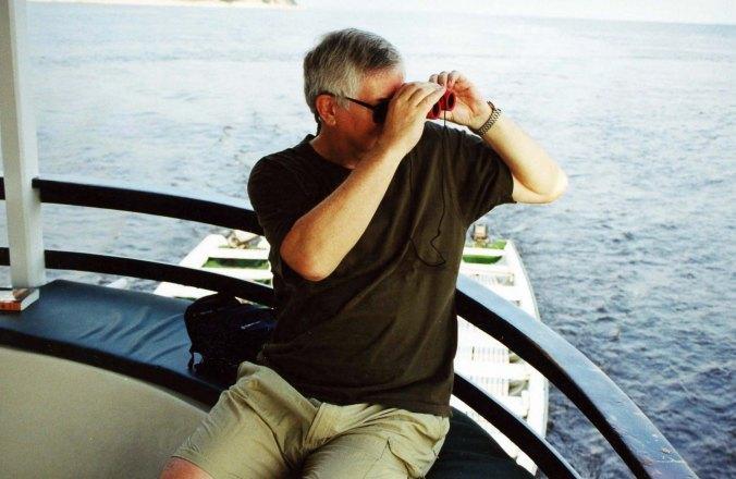Curt Mekemson searching for wildlife on Amazon River