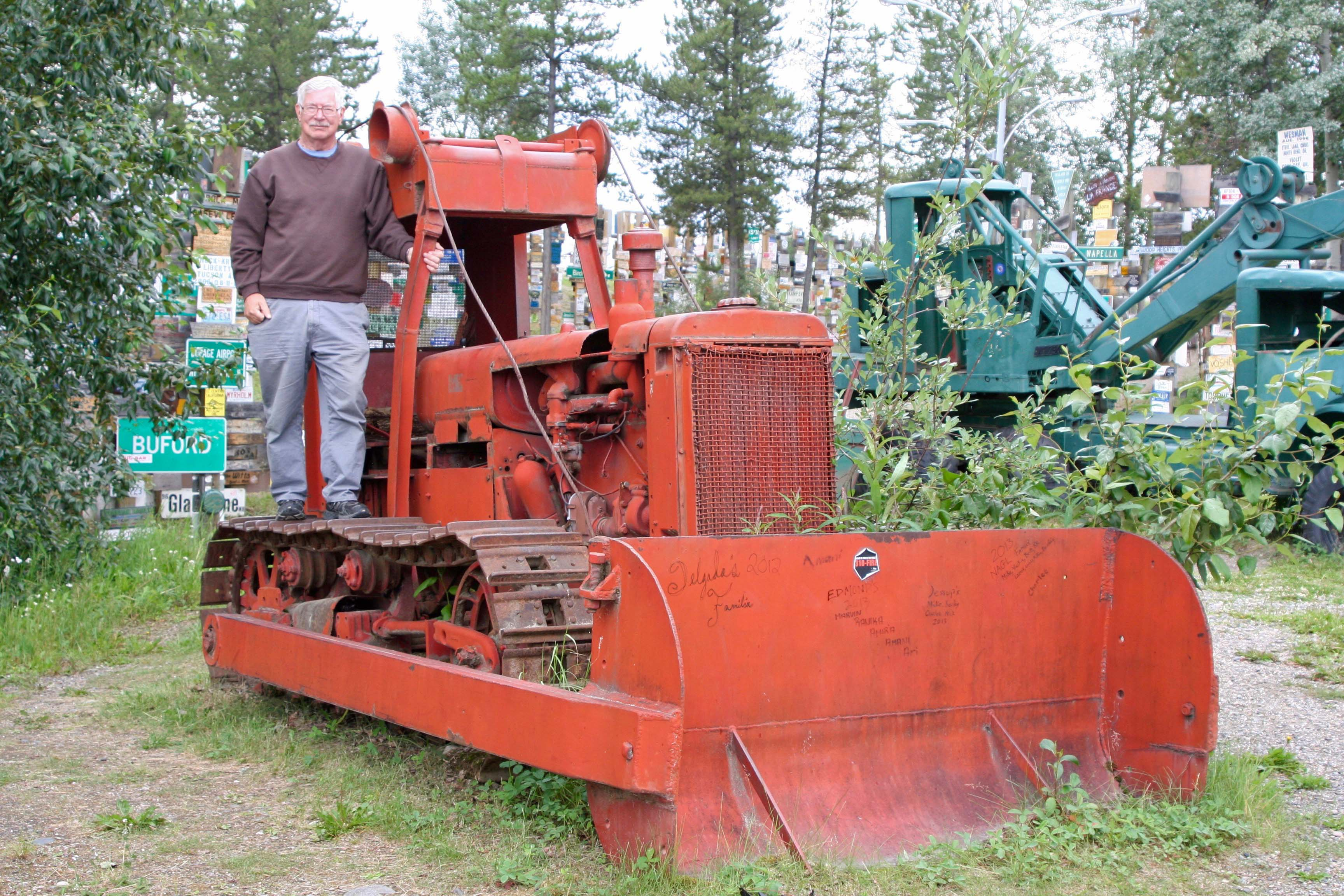Curt Mekemson standing on bulldozer used to build Alaska Highway