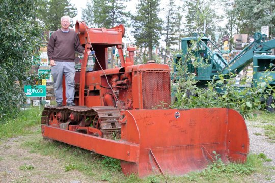 Curt Mekemson standing on bulldozer used to build Alaska Highway