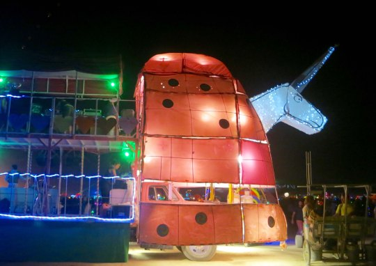 Large mutant vehicle unicorn at night at Burning Man.