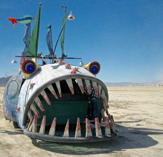 Mutant vehicle fish at Burning Man with large teeth.