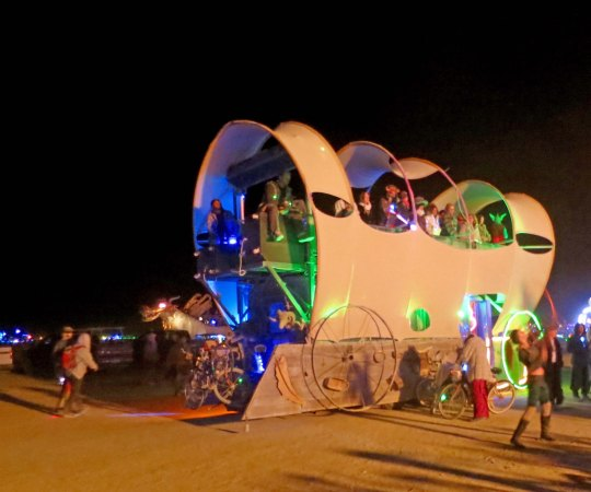 Conestoga Wagon mutant vehicle at Burning Man at night.