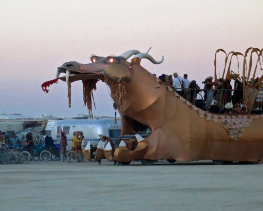 Golden dragon mutant vehicle at Burning Man with eyes glowing.