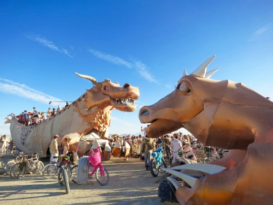 Golden dragon mutant vehicle at Burning Man with baby dragon.