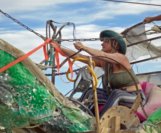 Burner uses cables to operate green mutant dragon at Burning Man.