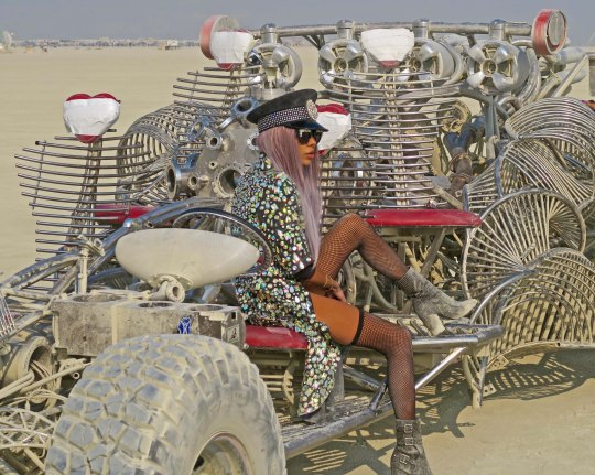 Mutant Vehicle hot rod at Burning Man with attractive woman.