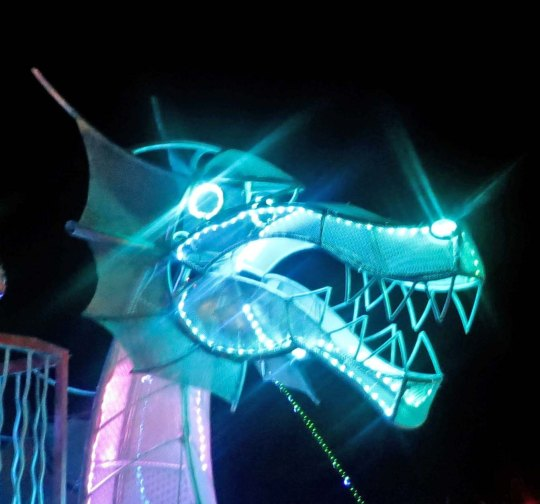 Striking green head of mutant vehicle dragon at night at Burning Man.