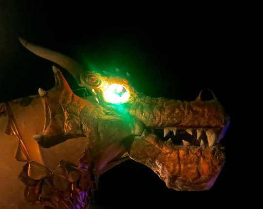 Mutant vehicle dragon with eyes glowing in the night at Burning Man.