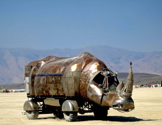 Large rhino mutant vehicle crosses the Playa at Burning Man.