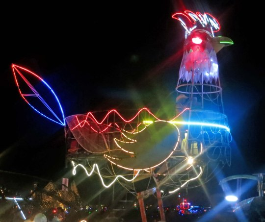 Rooster mutant vehicle at night at Burning Man.