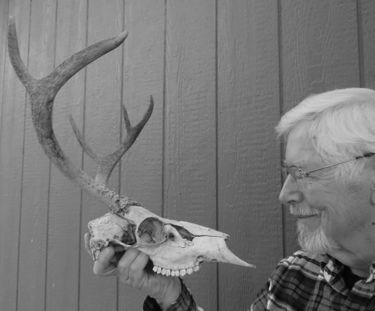 Photo of Curt Mekemson contemplating skull used to compare with Georgia O'Keefe contemplating skull.